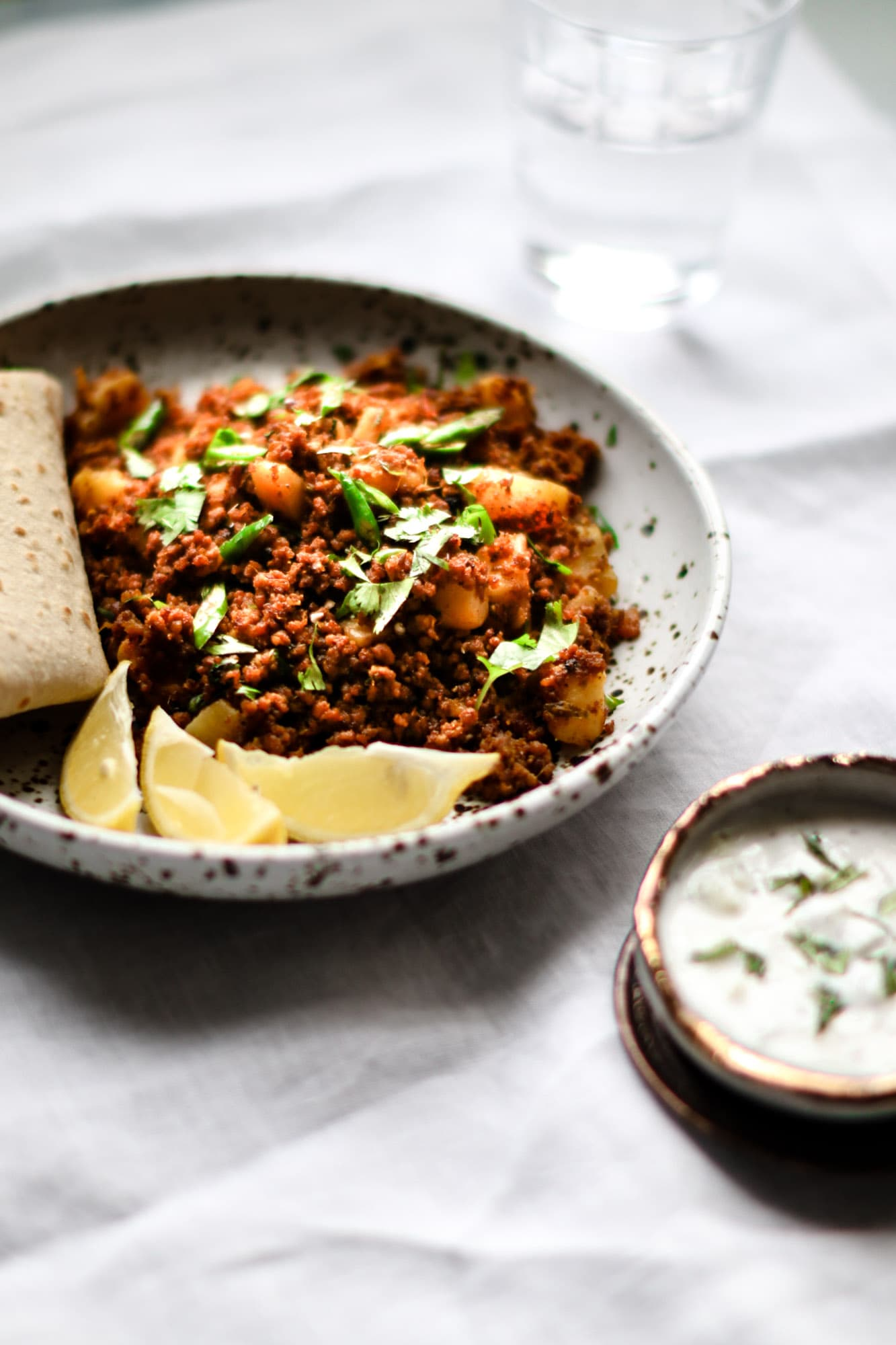 Close up of Aloo Keema with roti and lemon wedges on a speckled plate.