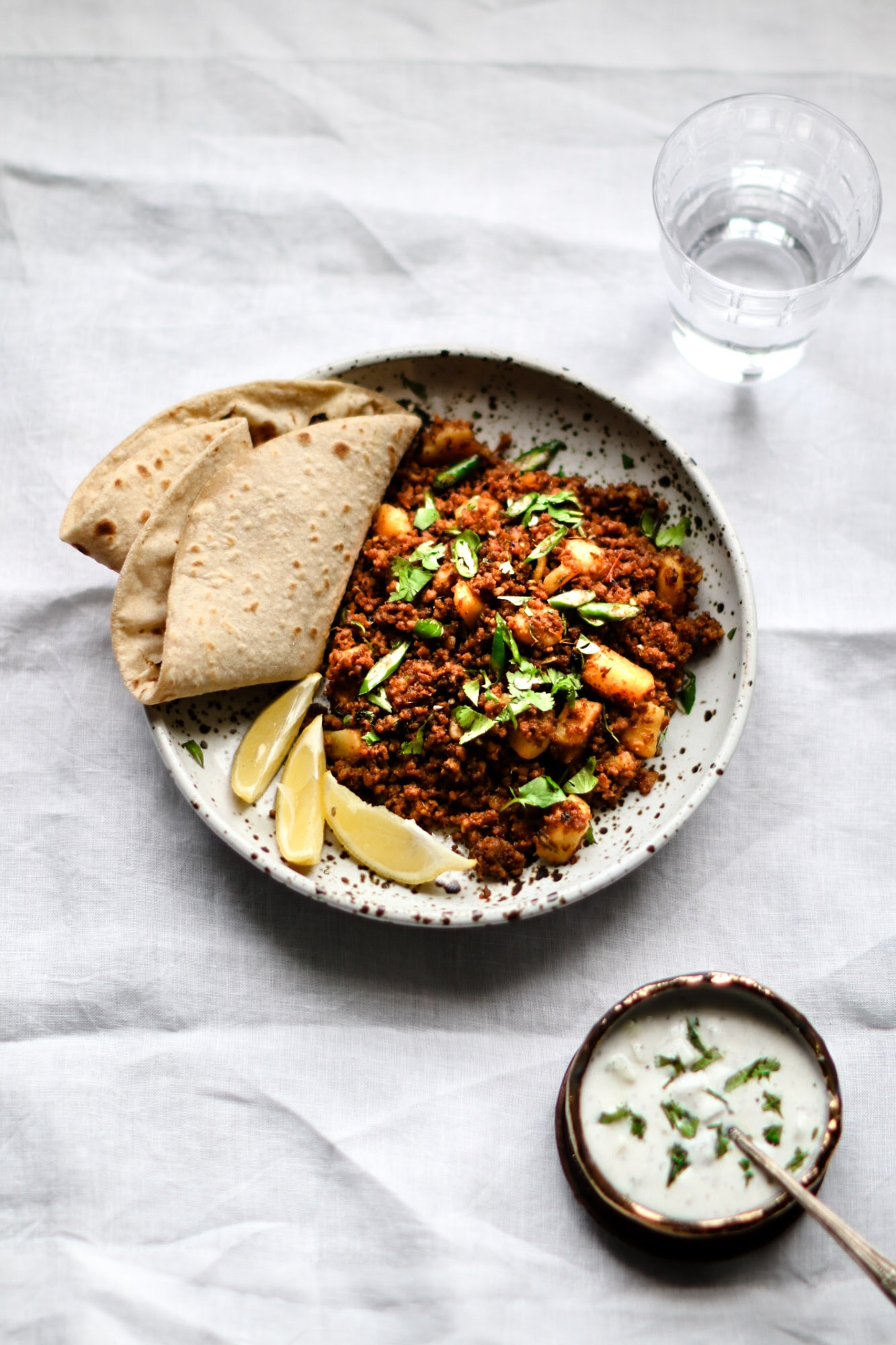 Aloo Keema with roti and lemon wedges on a speckled plate.