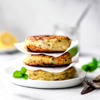 Stack of three Aloo Ki Tikkis (Pakistani-Style Potato Cakes) on a round white plate garnished with mint leaves.