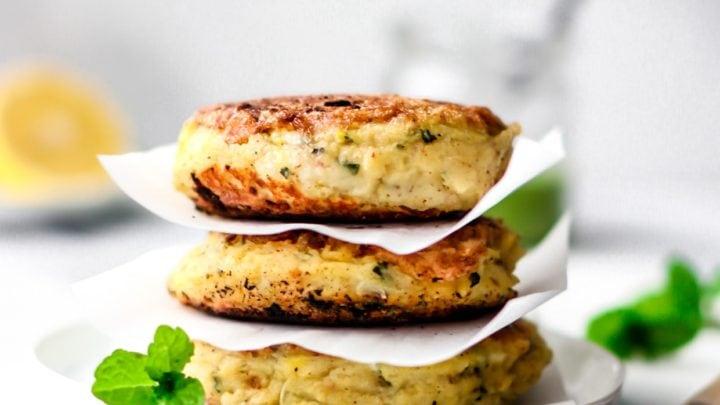 Stack of three Aloo Ki Tikkis (Pakistani-Style Potato Cakes) on a round white plate garnished with mint leaves.