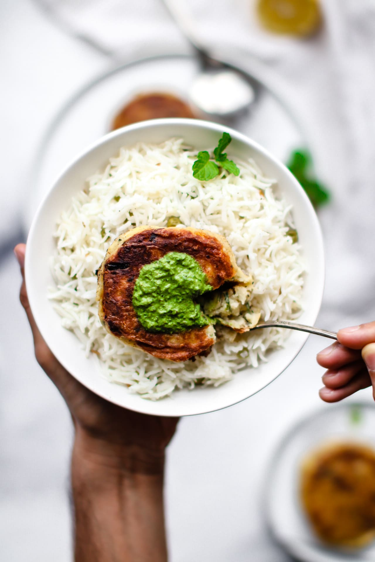 Eating an Aloo Ki Tikki (Pakistani-Style Potato Cake) spread with green chutney in a white bowl filled with basmati rice.