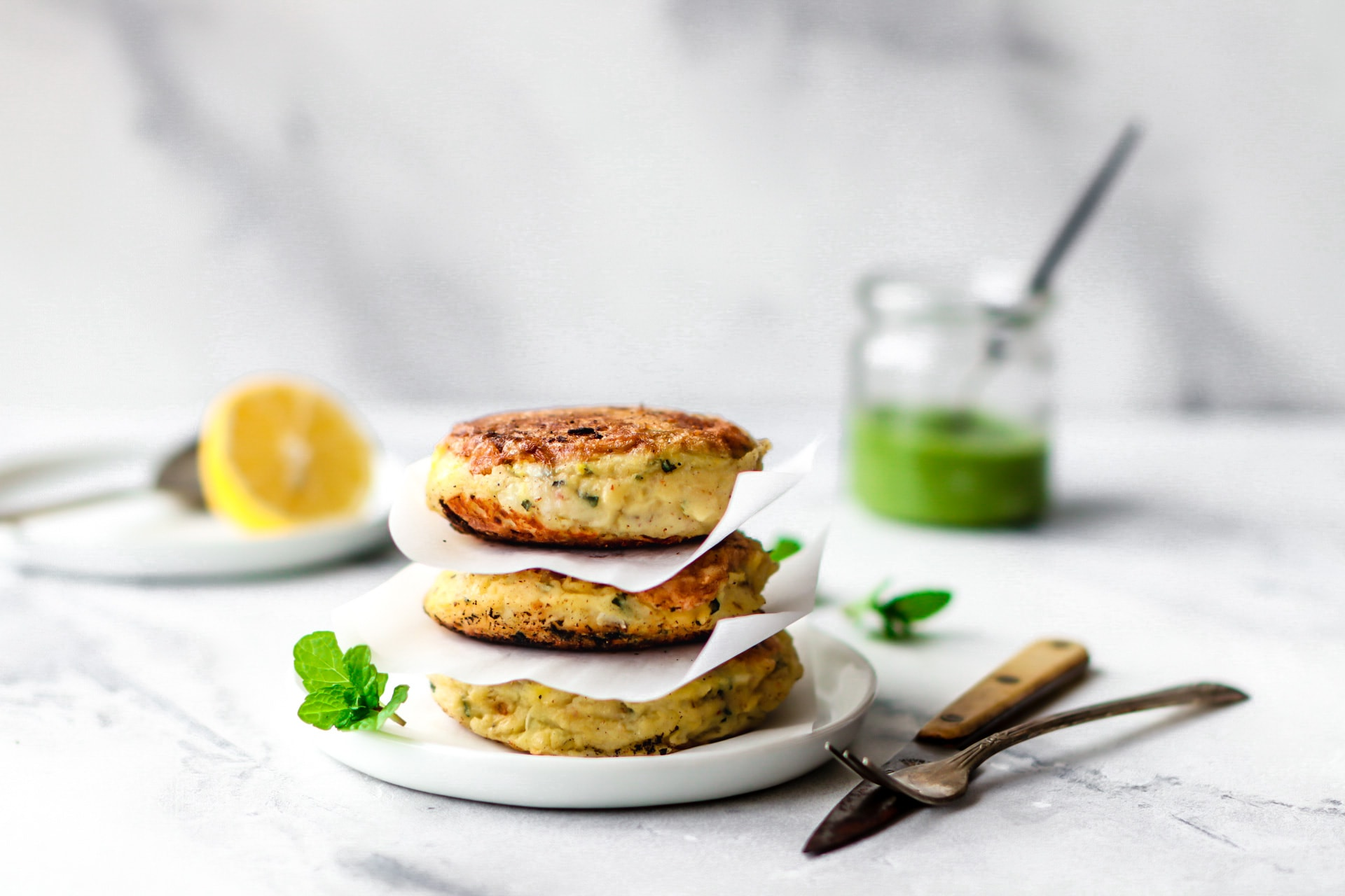 Stack of three Aloo Ki Tikkis (Pakistani-Style Potato Cakes) on a round white plate garnished with mint leaves and a jar of green chutney in the background.