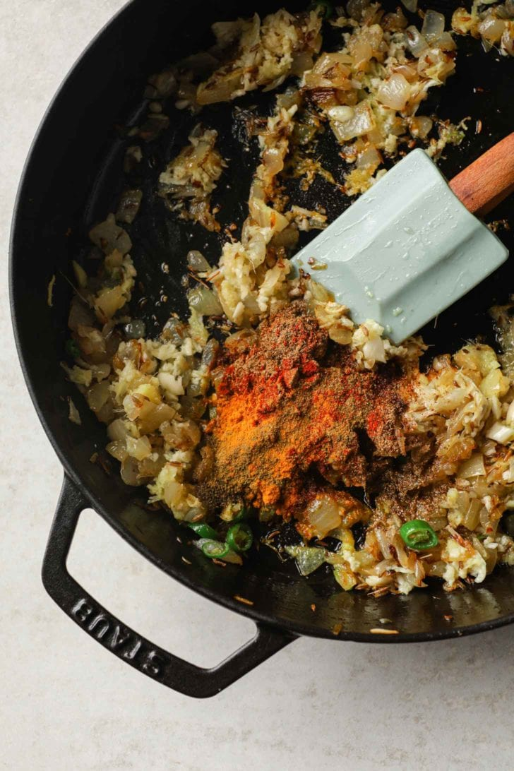 spices added to a base of browned onions in a skillet