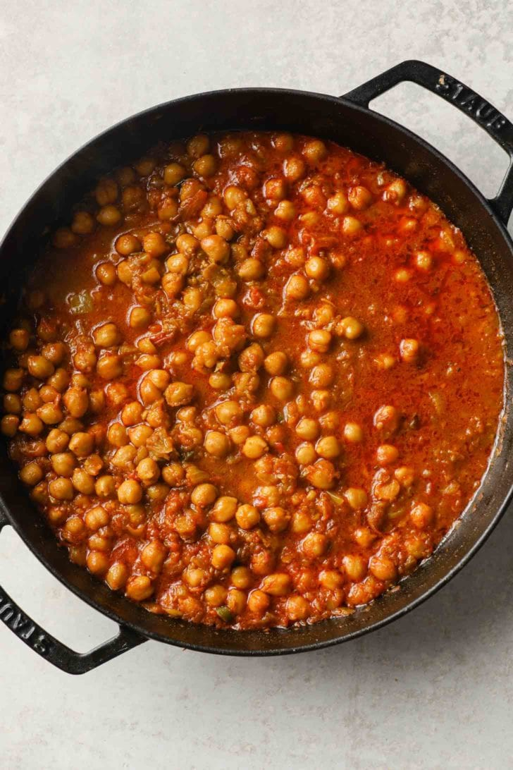 cooked chickpea curry in  a black skillet