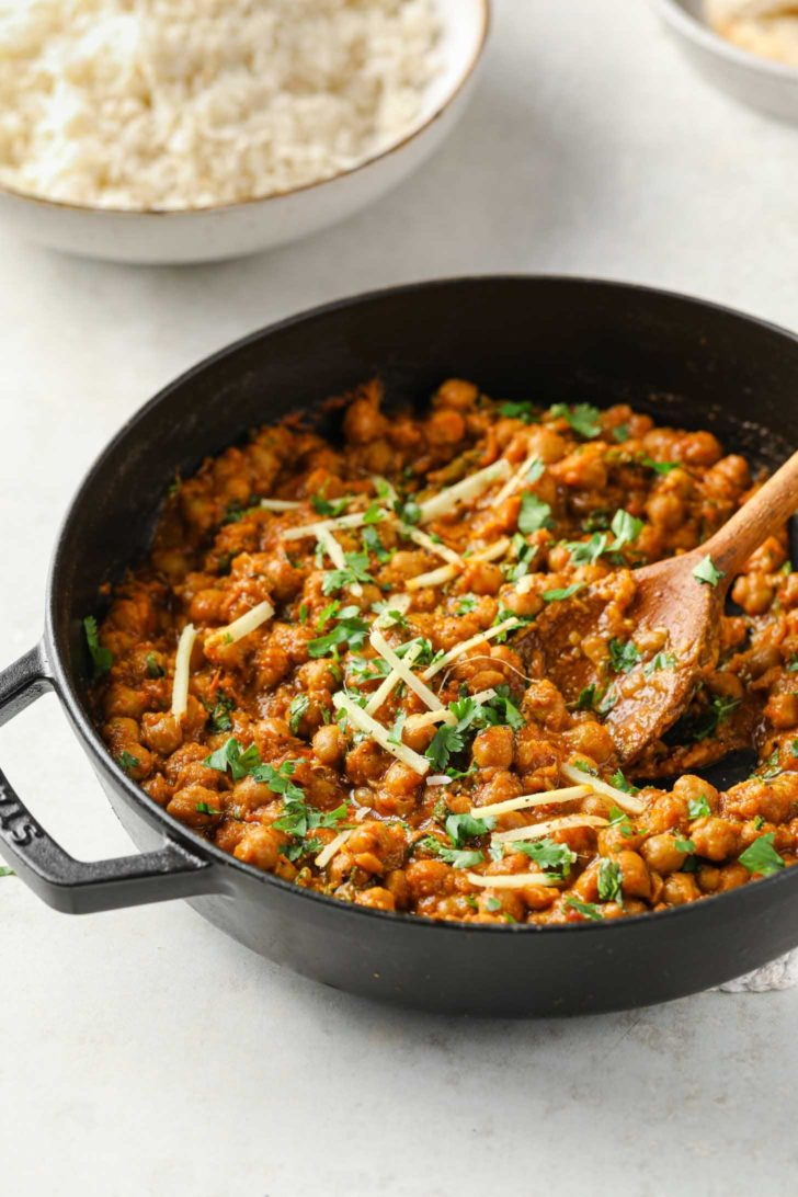 Authentic Chana Masala garnished with cilantro and julienned ginger in a black skillet