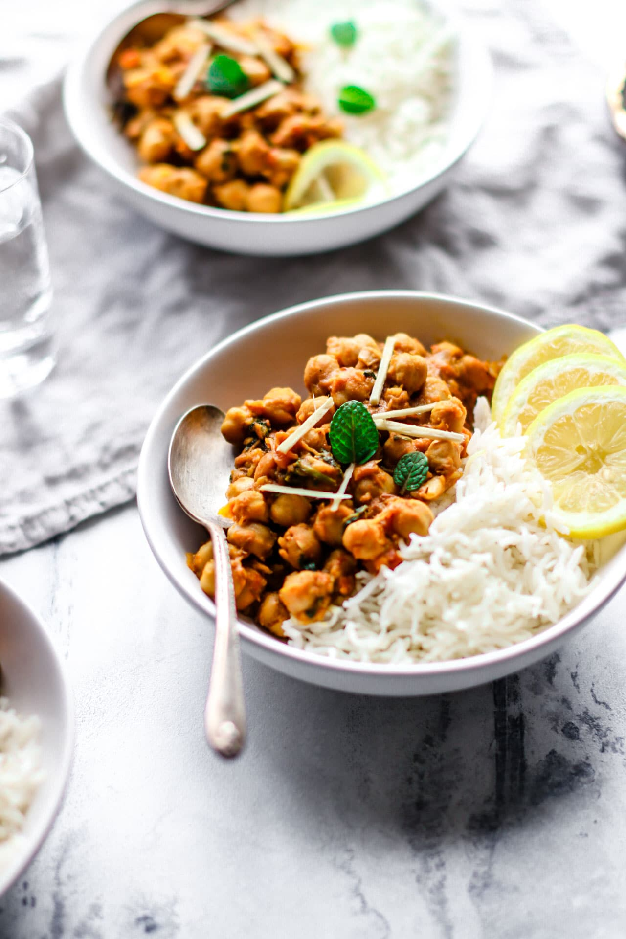 A white bowl with chana masala, rice, and lemon with a silver spoon inside.