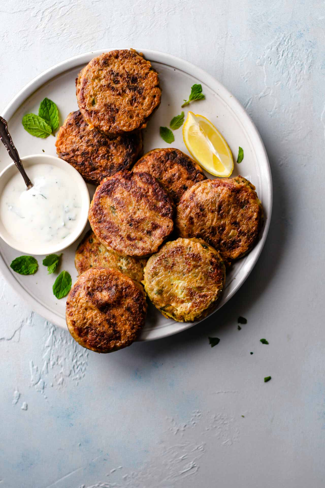 Shami Kebabs in a plate with raita and lemon on the side