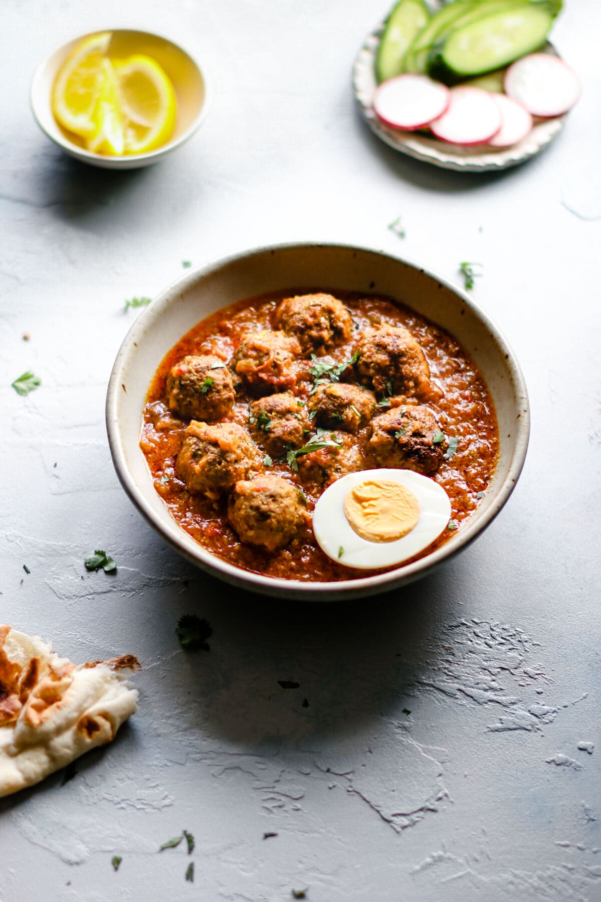 A bowl of  Pakistani Beef Kofta Curry garnished with half a hard boiled egg and cilantro.