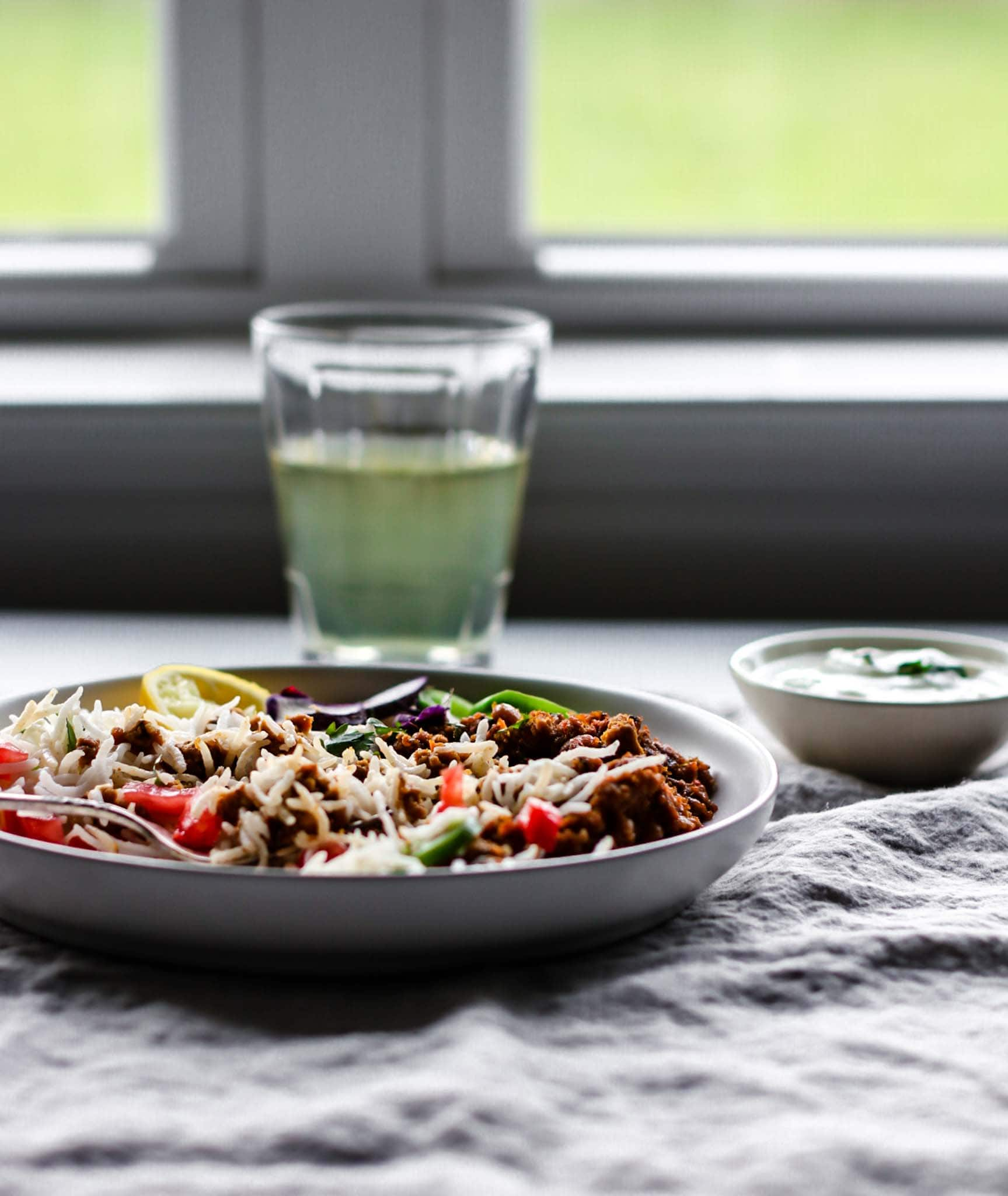 A plate of Keema Lobia with a silver fork with rice, vegetables placed in front of a window.
