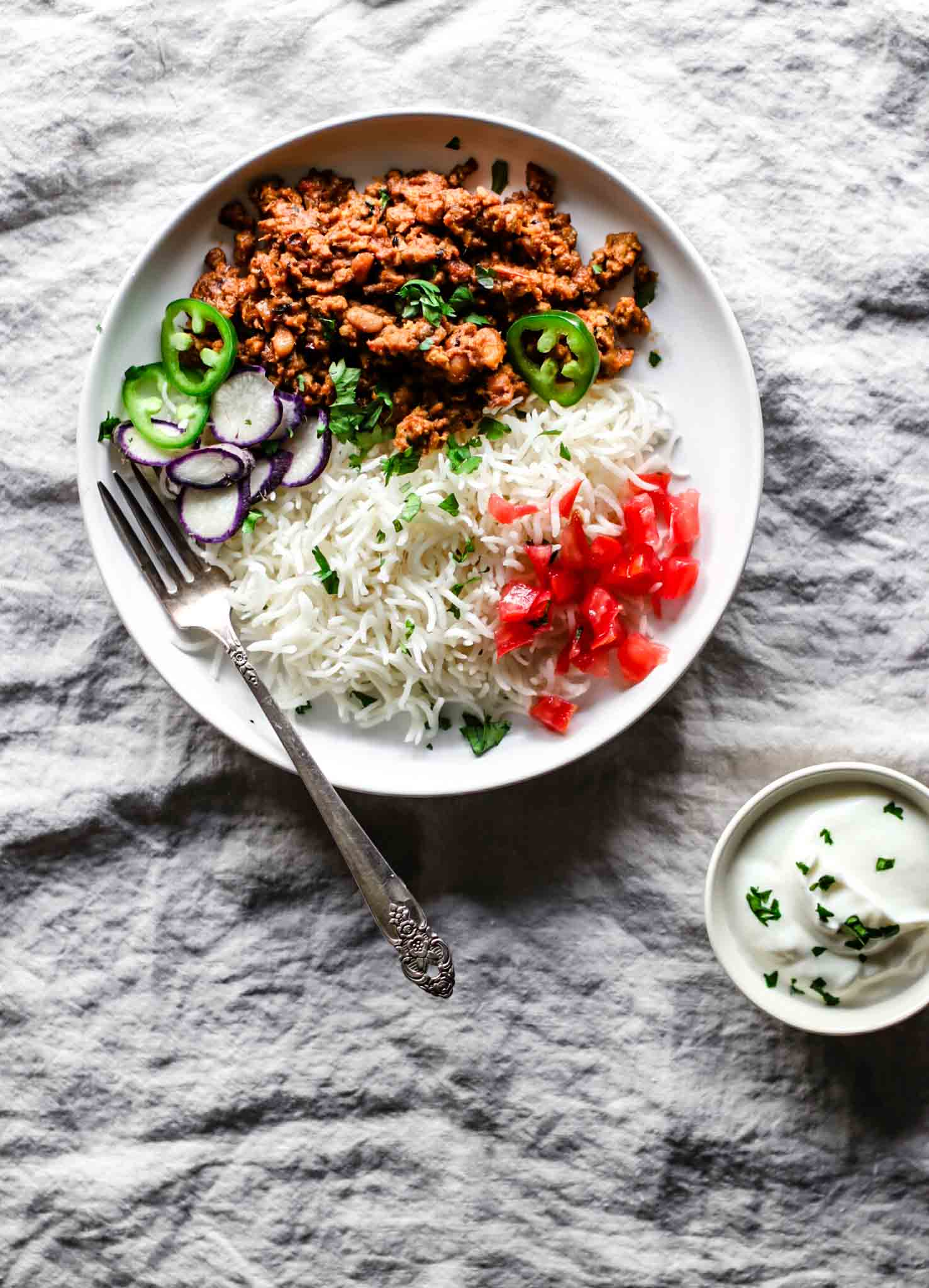 Keema Lobia on a white plate with a silver fork with rice, vegetables, and yogurt on the side