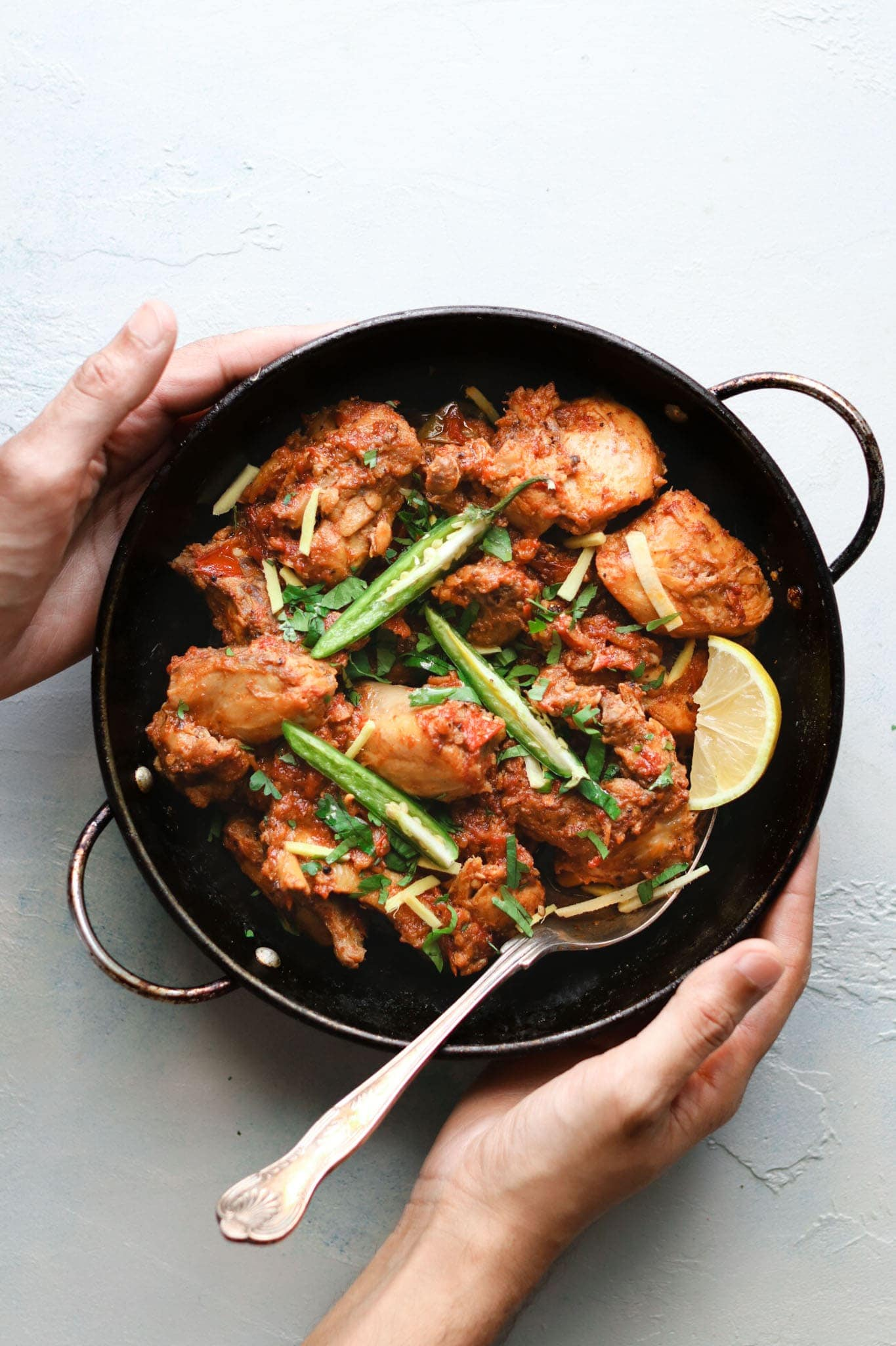 Holding Chicken Karahi in a karahi
