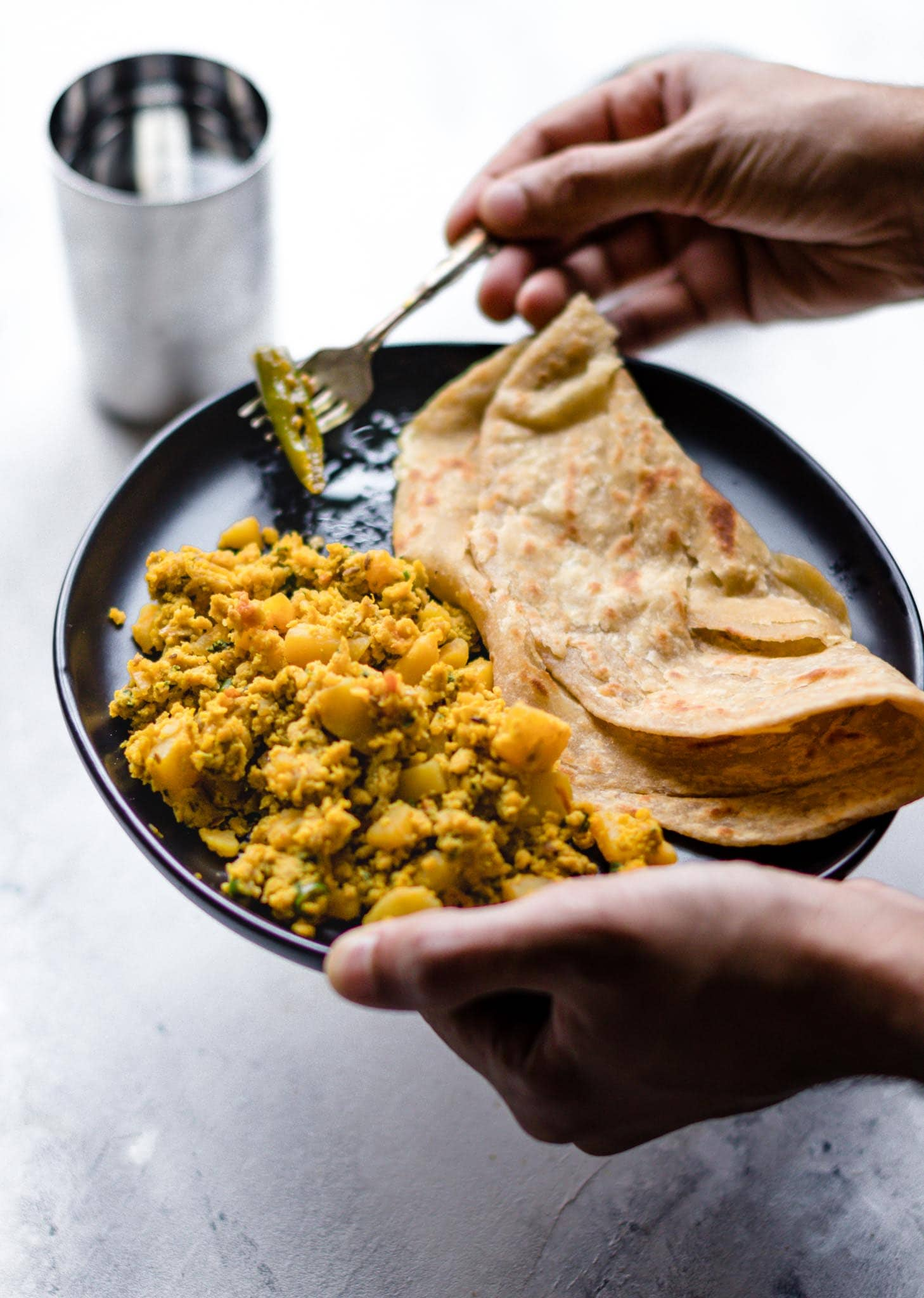 Holding a fork and a plate of scrambled egg and potatoes with paratha