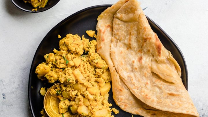 Scrambled Egg and Potatoes and paratha on a black plate with a gold spoon