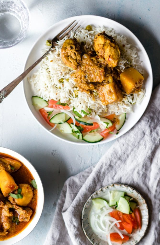 Chicken curry with potatoes on a plate with rice and fork