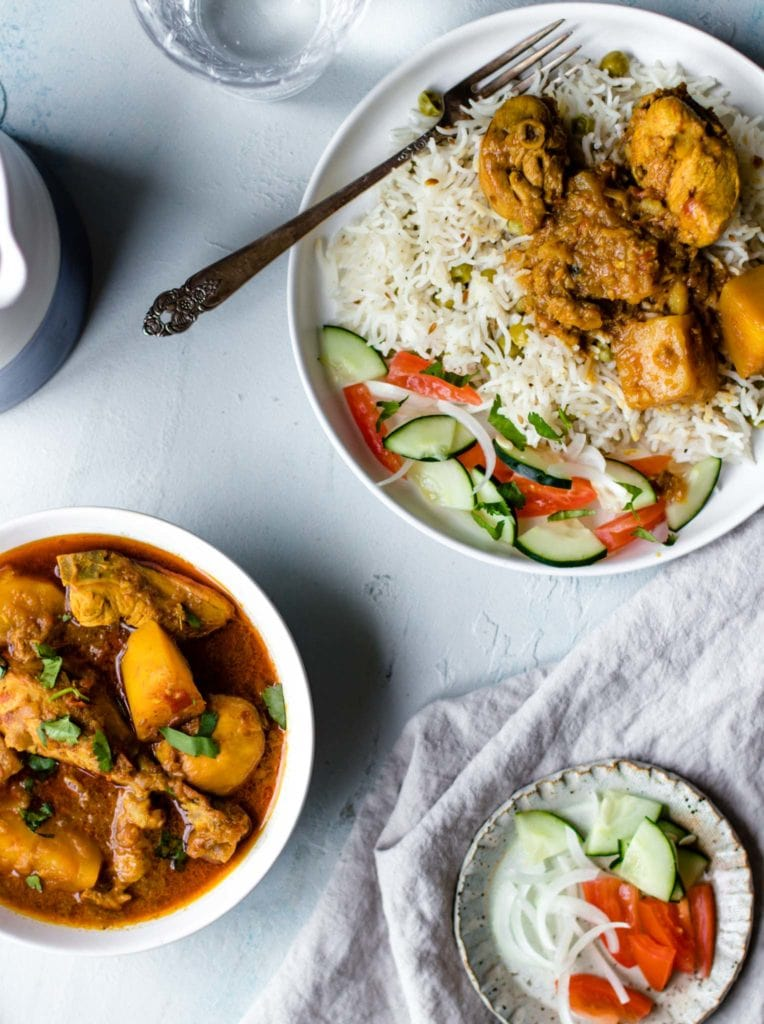 Aloo Chicken (Chicken and Potato Curry) in a bowl and on a plate with rice and vegetables