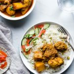 Chicken Curry with potatoes on a plate with rice and vegetables with a glass of water on the side