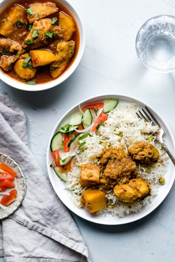 Pakistani Chicken Curry with potatoes on a plate with rice and vegetables with a glass of water on the side