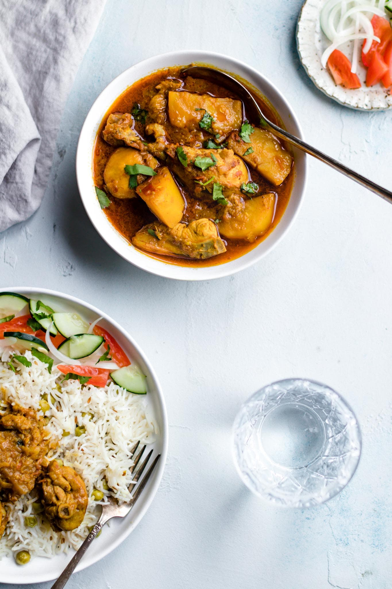 A white bowl with authentic Pakistani chicken curry and a spoon inside