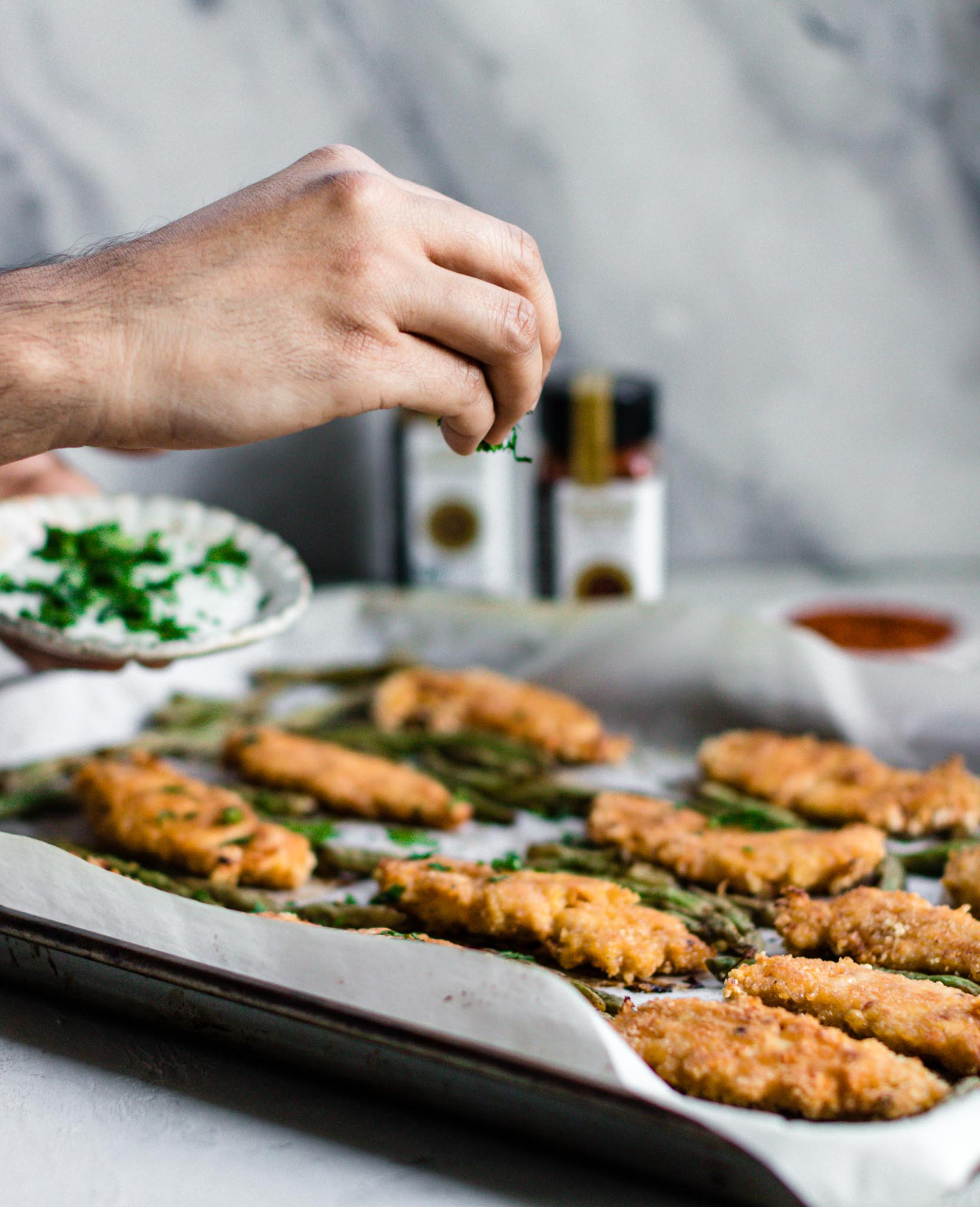 Sprinkling cilantro on top of a parchment lined baking sheet with Baked Peri Peri Chicken Tenders with Masala Green Beans.