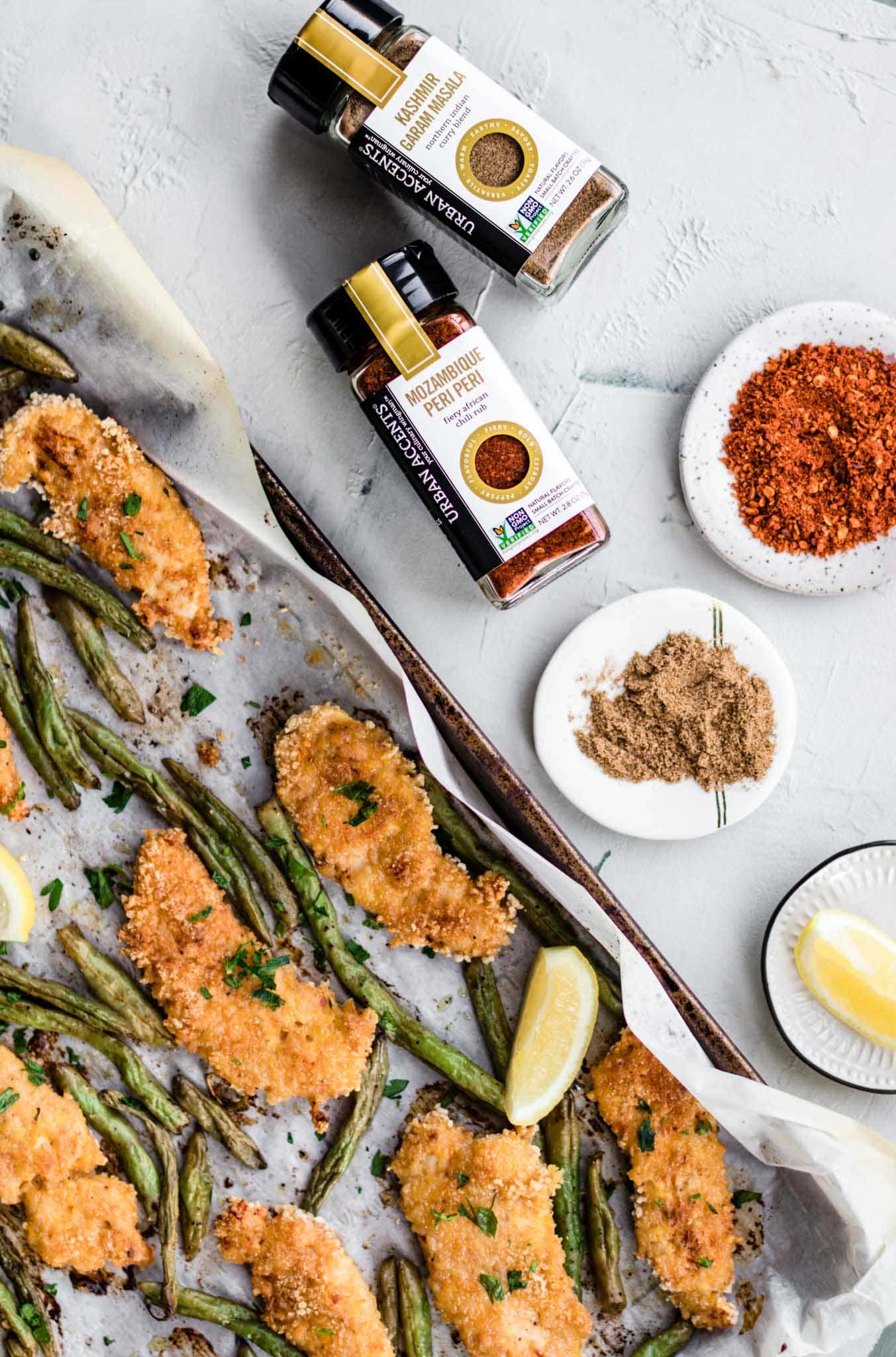 A parchment lined baking sheet with Baked Peri Peri Chicken Tenders and Masala Green Beans beside dishes containing Mozambique Peri Peri and Garam Masala spice blends.