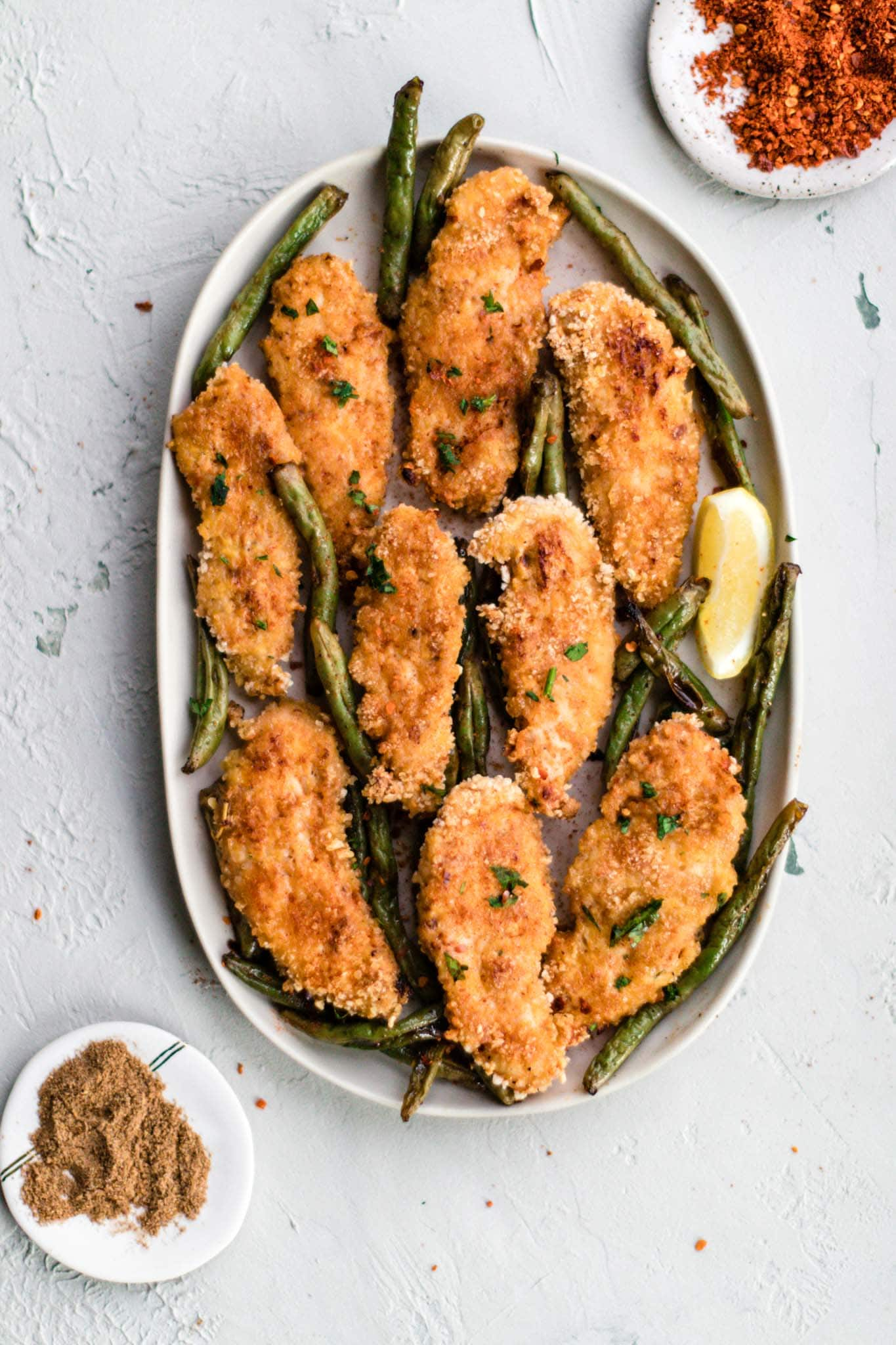 Baked Peri Peri Chicken Tenders with Masala Green Beans on an oval white platter garnished with a wedge of lemon.