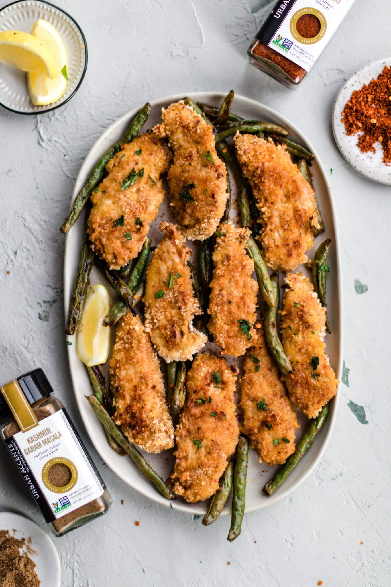 Baked Peri Peri Chicken Tenders with Masala Green Beans garnished with a lemon wedge on a white oval platter alongside jars of Mozambique Garam Masala and Peri Peri Spice Blends.