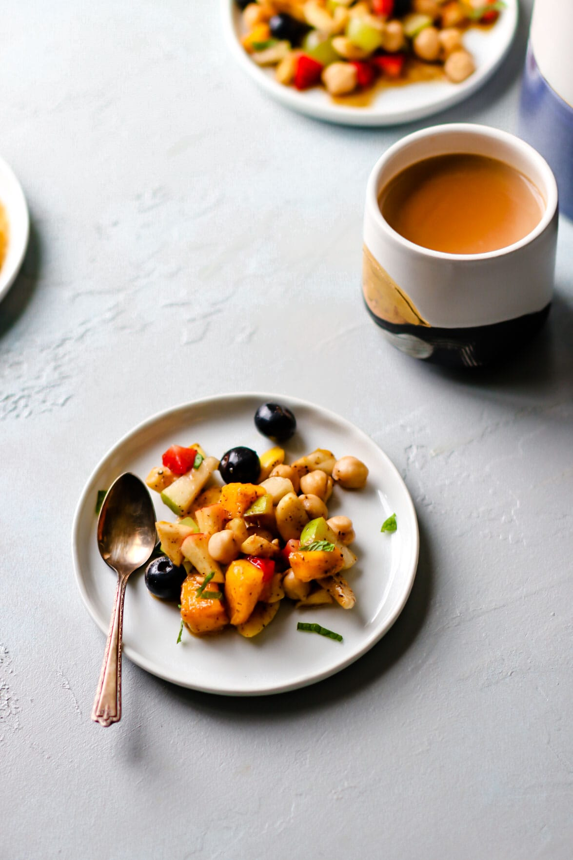 Fruit Chaat on a white plate with a spoon and chai on the side