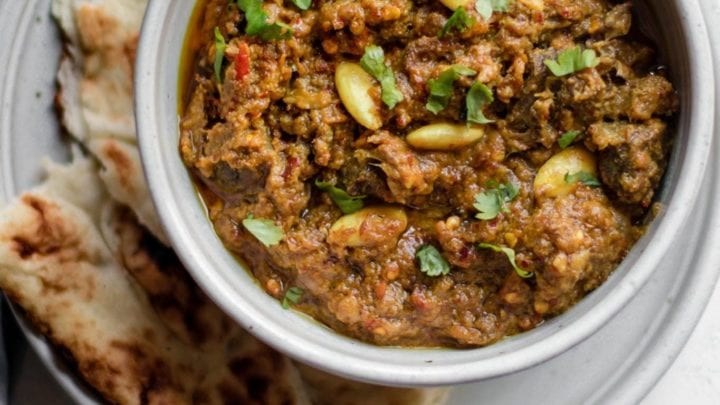 Pakistani Beef Curry (Stew) in a bowl on top of a plate with naan