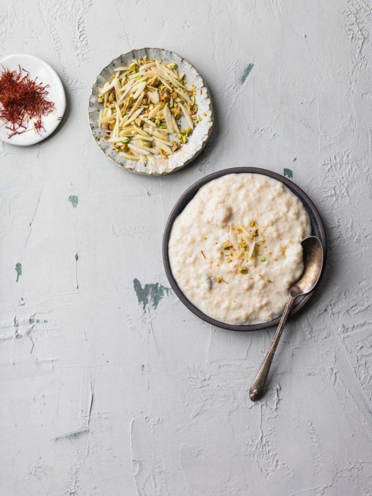 Kheer on a dark plate with a spoon along with pistachios and almonds and saffron strands