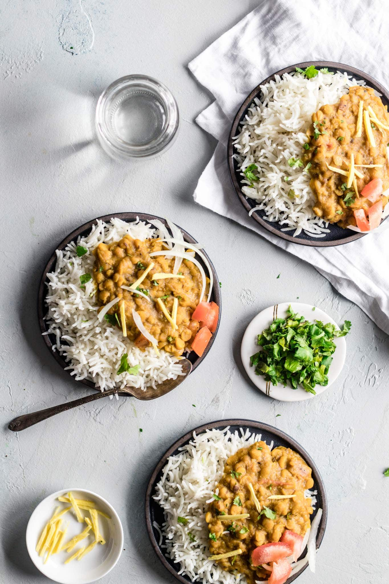 Chana Dal in plates garnished with ginger, onions, and tomatoes with a side of basmati rice
