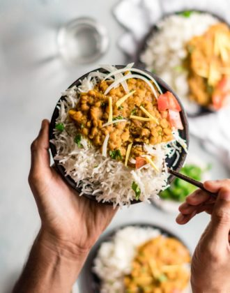 Holding a plate of chana dal with a spoon in it