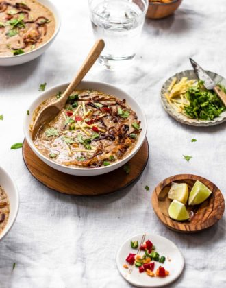 Instant Pot Pakistani-style Haleem made with beef and grains in a white bowl with wooden spoon and garnishing