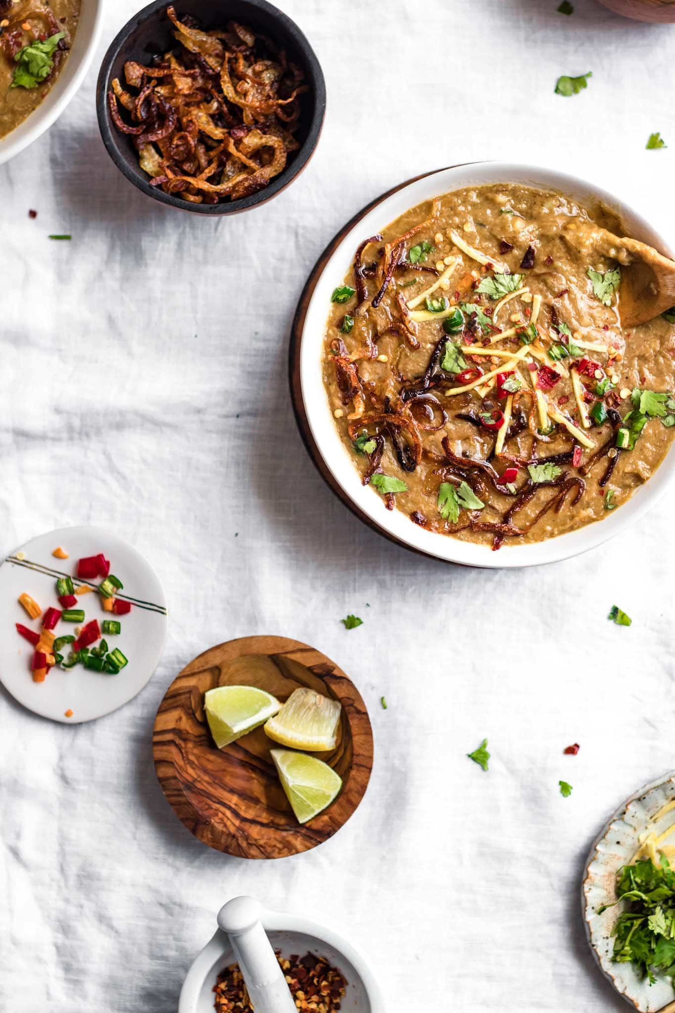 Pakistani Haleem recipe with fried onions, chili peppers, and lemon on the side
