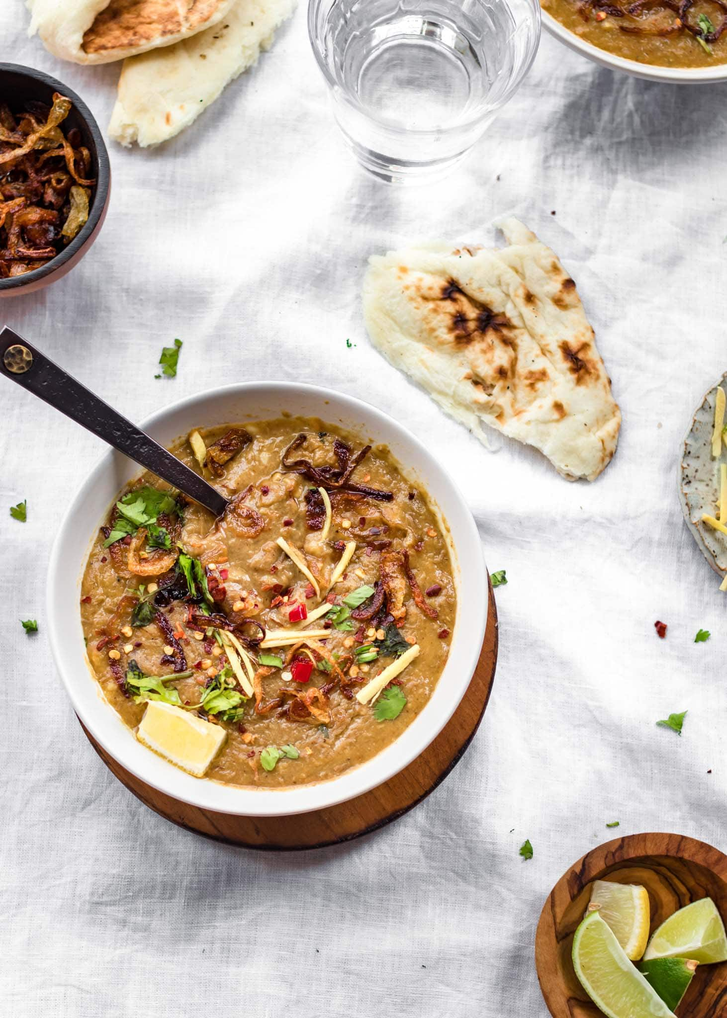 Instant Pot Haleem in a bowl with a black spoon and naan on the side