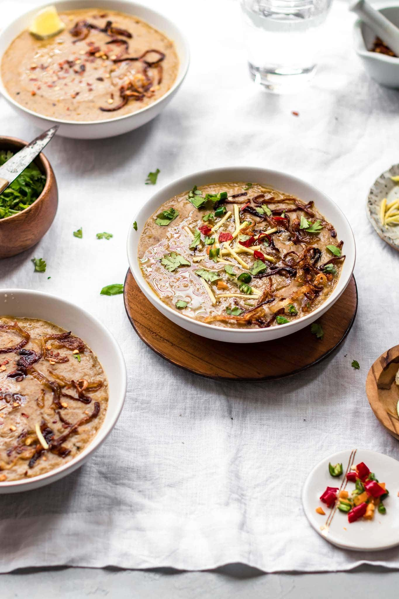 Haleem (Pakistani beef and lentil stew) in a white bowl with garnishing on top