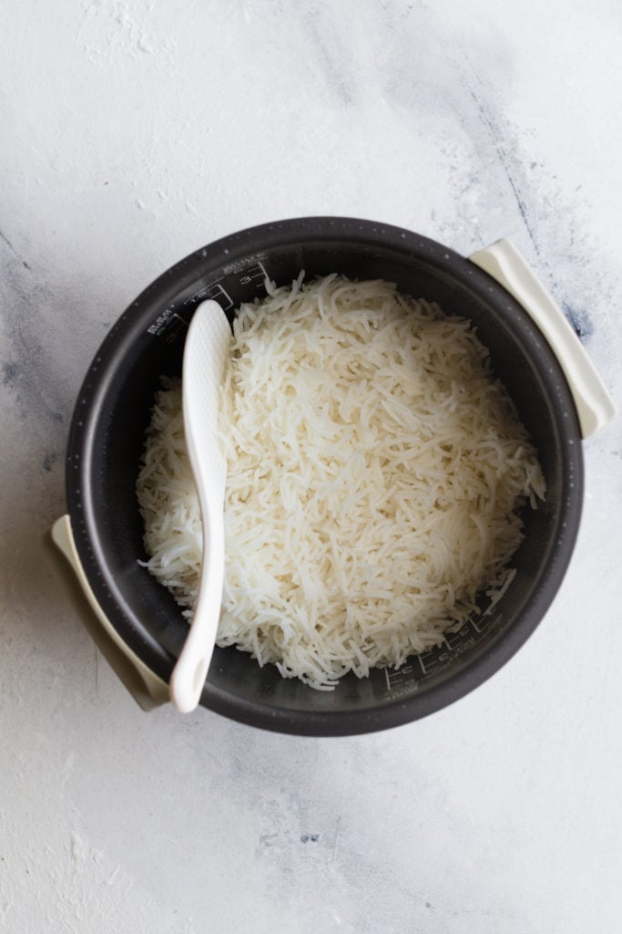 Fluffed basmati Rice with a rice paddle inside a rice cooker bowl