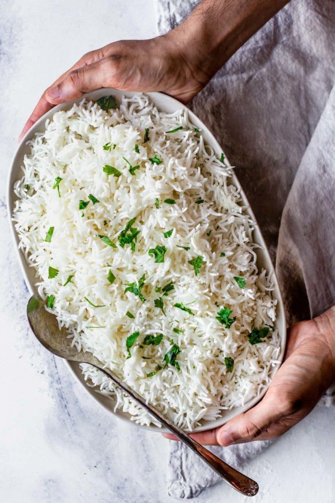 Holding Basmati Rice in a platter with a silver spoon
