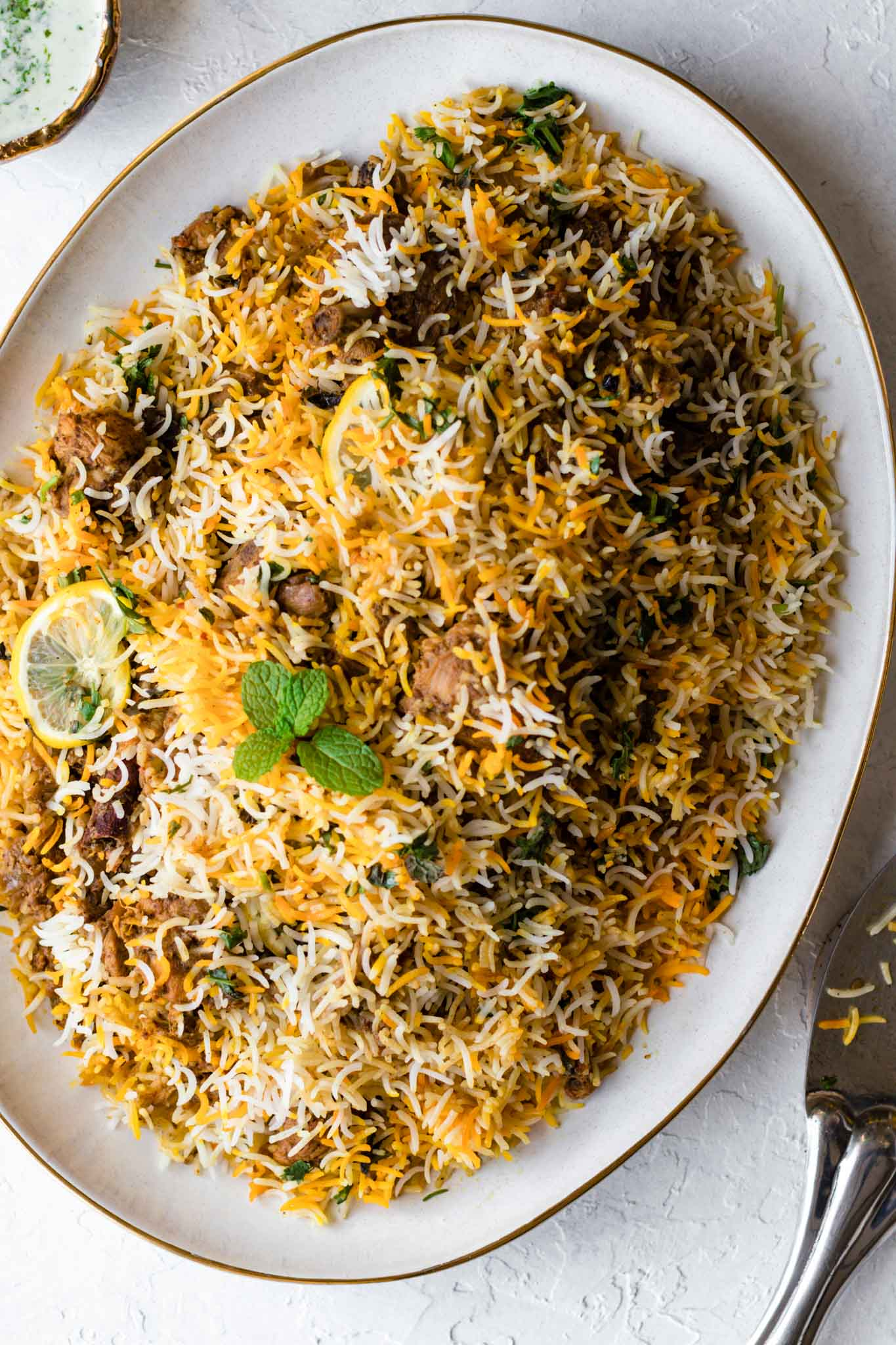 Chicken Biryani on a large, gold-trimmed platter garnished with mint and lemons with yogurt raita and a traditional serving spoon on the side