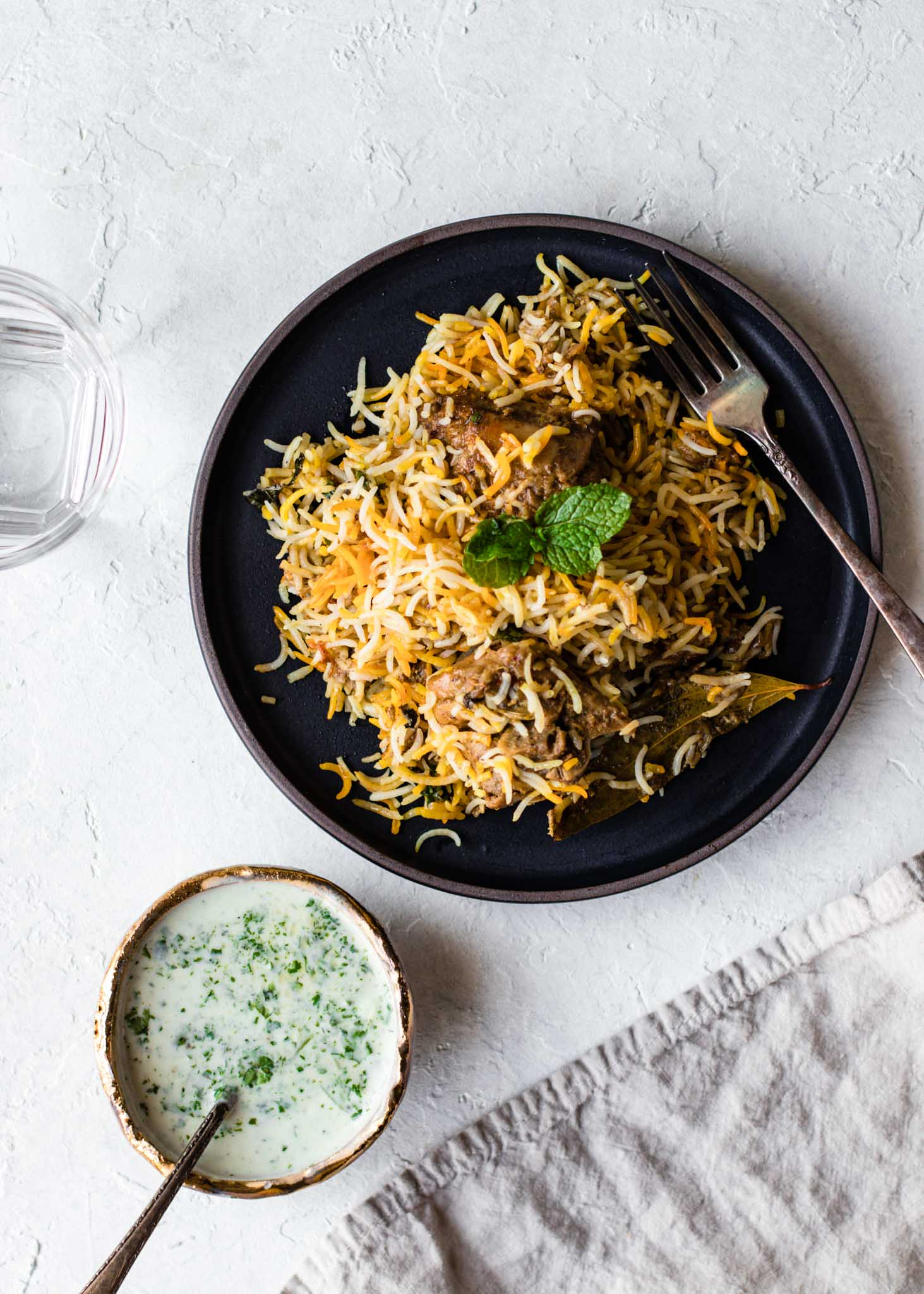 Chicken Biryani in a black plate with multi-colored rice garnished with mint and served with yogurt raita on the side