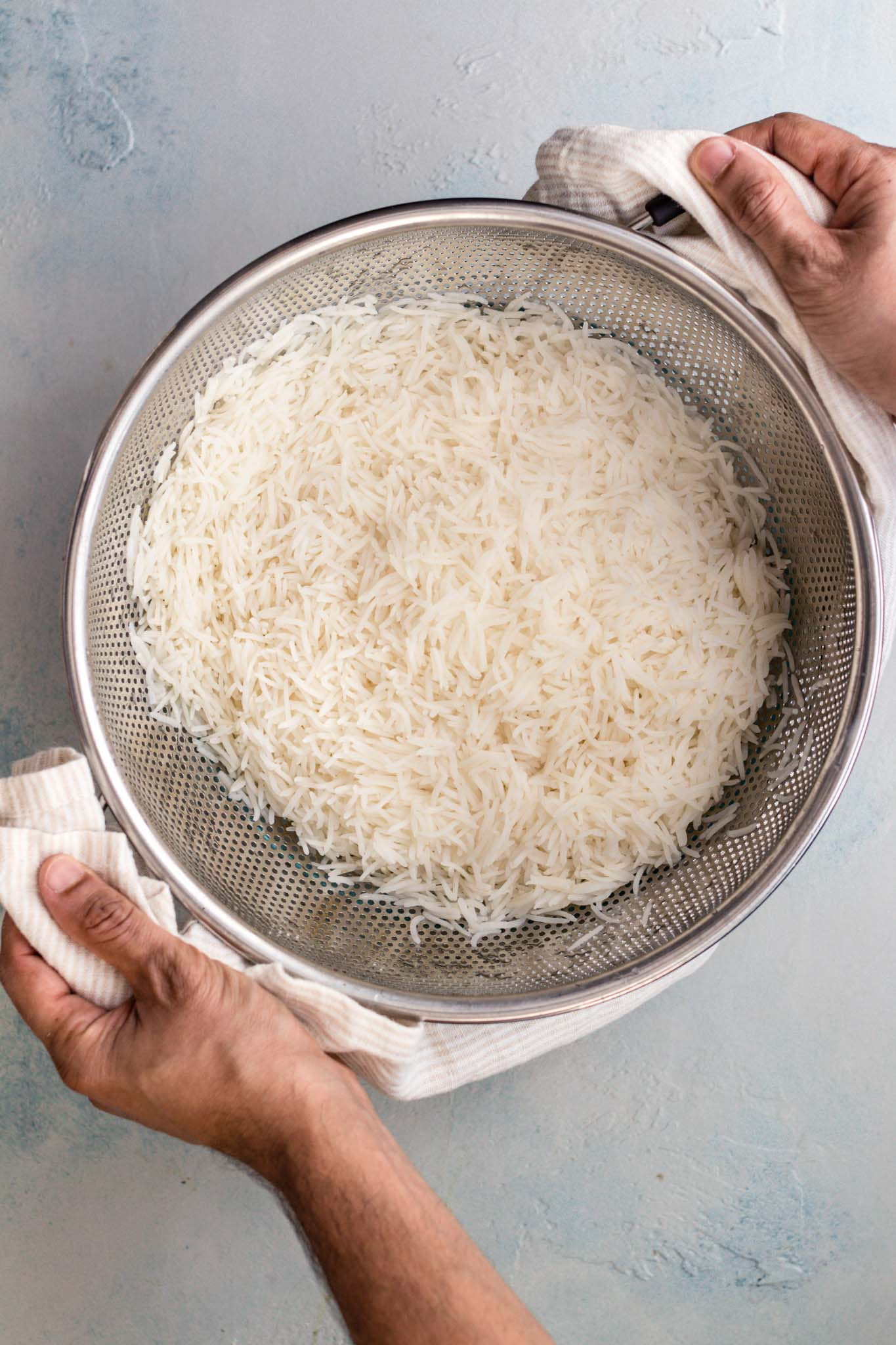 Holding par-boiled rice for biryani on a colander or sieve