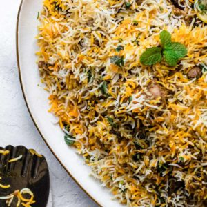 Chicken Biryani on a gold-trimmed platter with a silver rice spoon resting on the side
