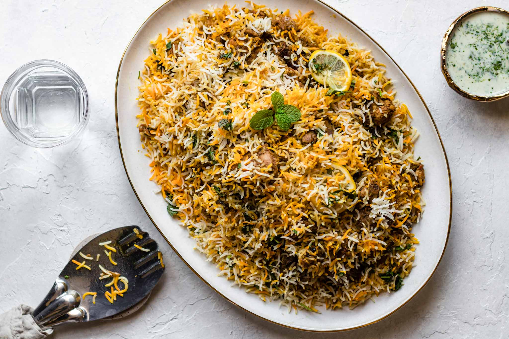 Chicken Biryani on a large platter with a rice spoon, a glass of water, and yogurt raita on the side
