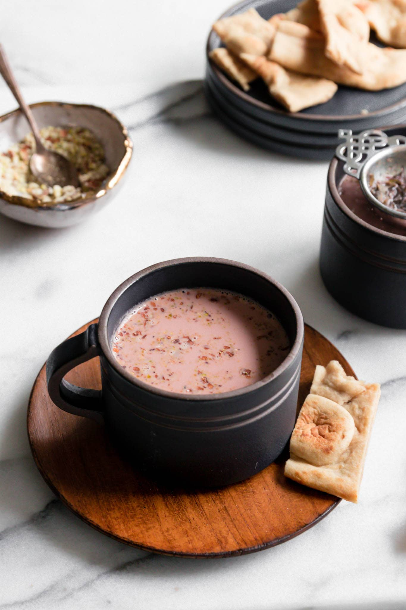 Dark cups filled with pink Kashmiri Chai garnished with nuts and served with a broken piece of naan