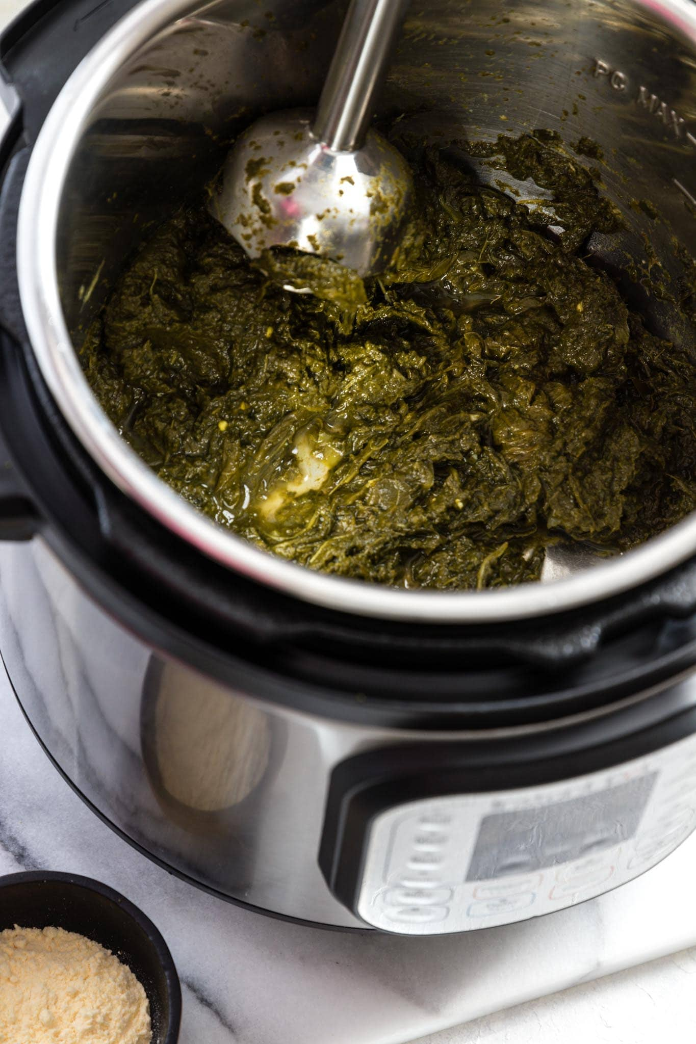 Blending greens for Instant Pot Sarson Ka Saag with a hand blender
