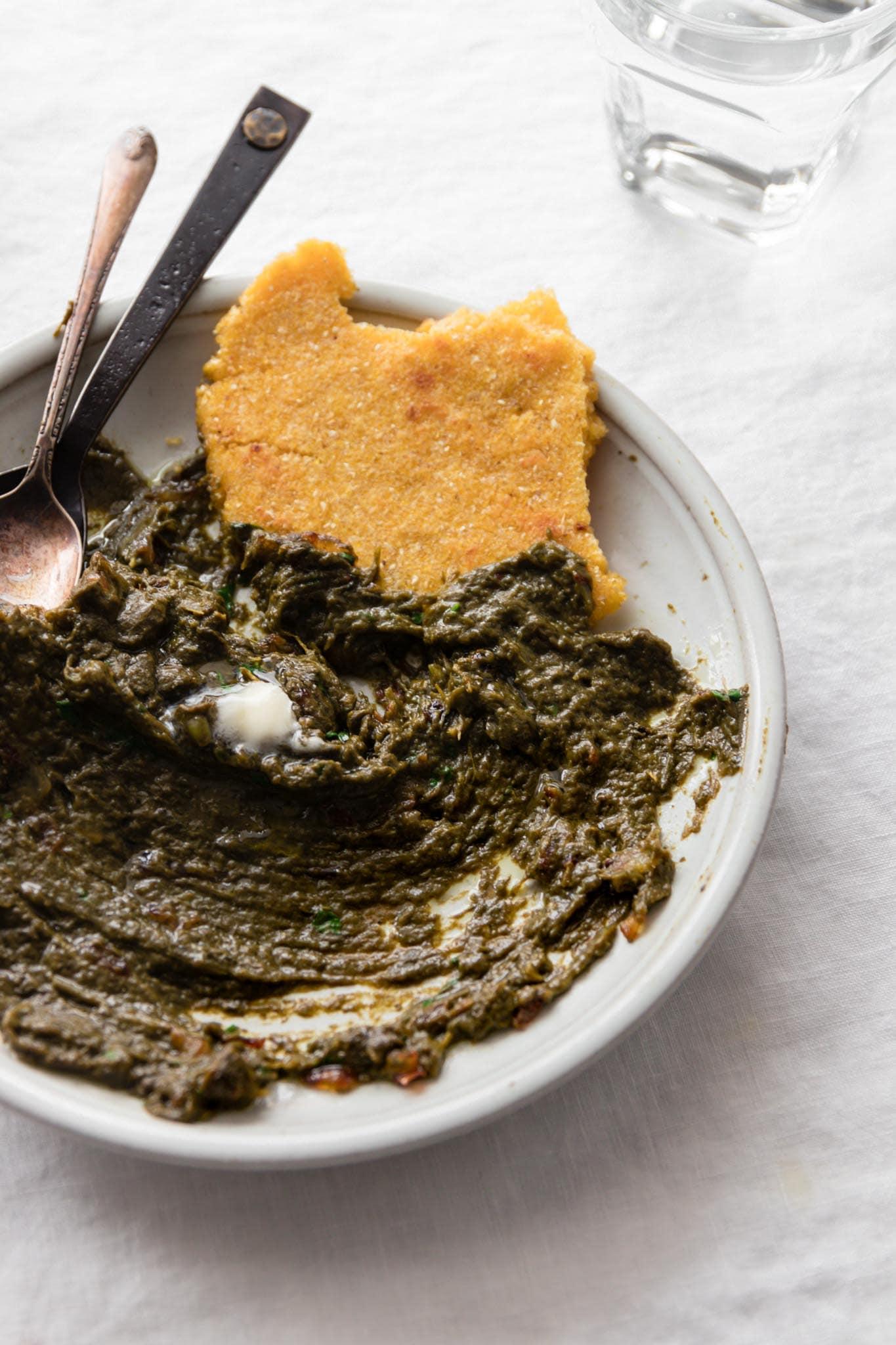Half eaten plate of Sarson Ka Saag served with Makai ki roti (cornmeal flatbread)