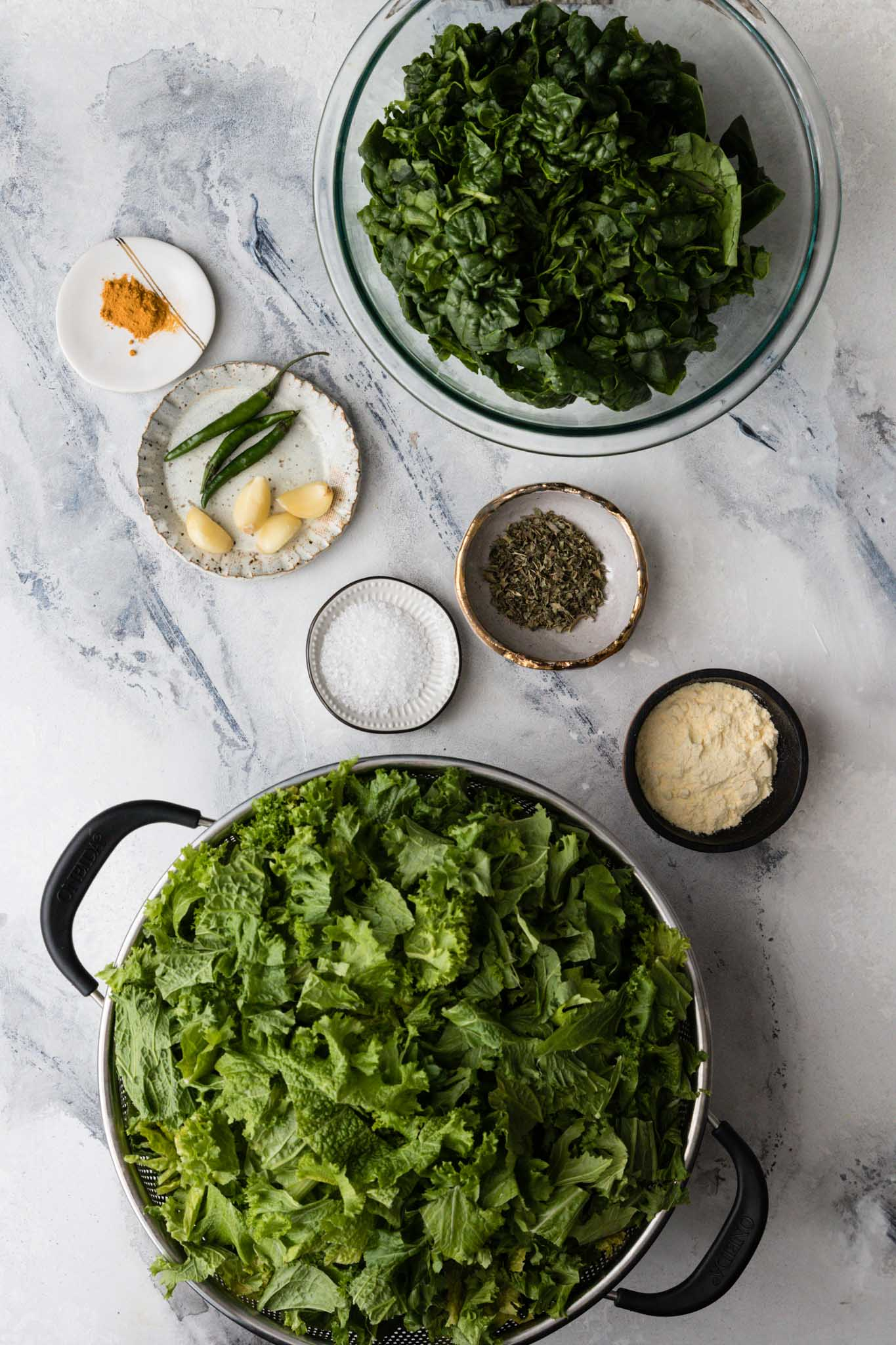 Marbled backdrop with ingredients for making Instant Pot Sarson Ka Saag