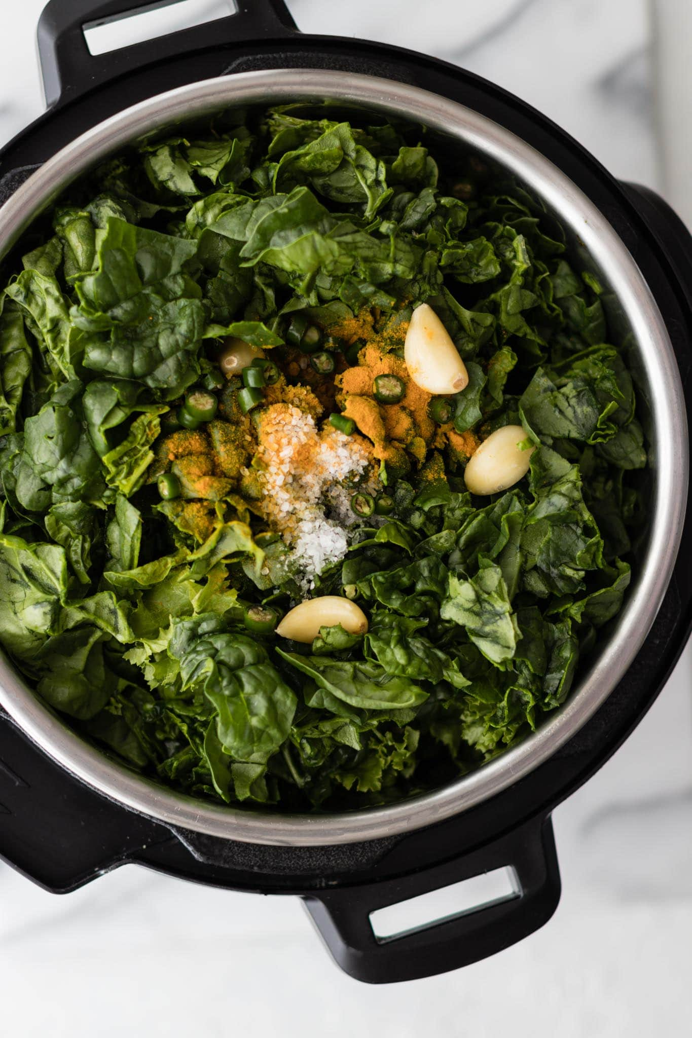Instant Pot filled with mustard greens and spinach, garlic, green chili pepper and turmeric ready to be cooked to make Sarson Ka Saag
