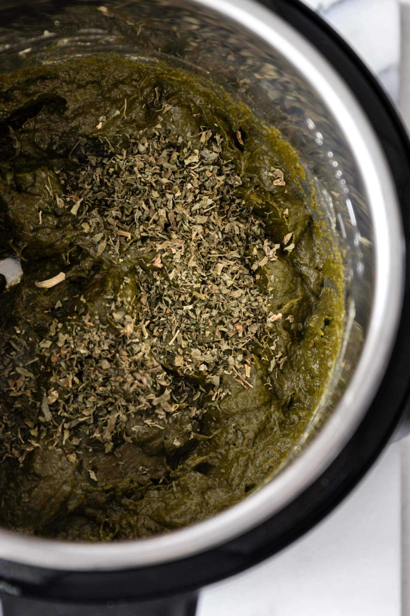 Adding dried fenugreek leaves (methi) to the Instant Pot for Sarson Ka Saag