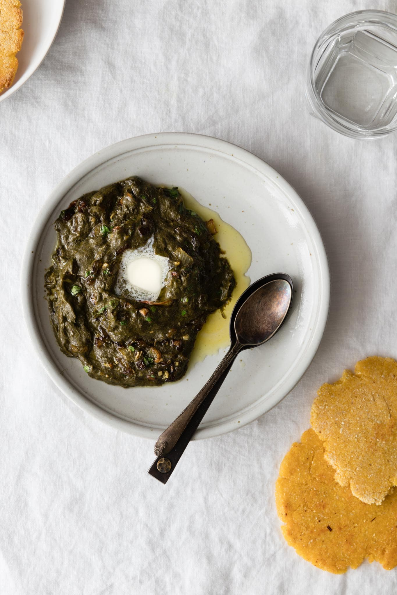 Sarson Ka Saag on a plate with a dollop of butter with makai ki roti on the side