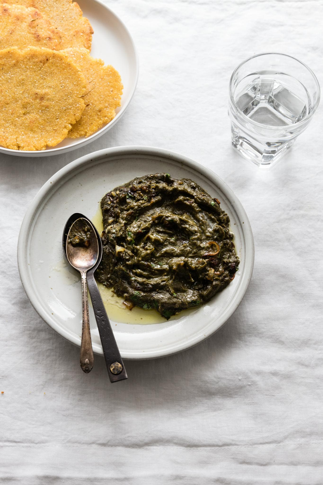 Easy Sarson Ka Saag on a plate with a couple spoons on the side served with makai ki roti (cornmeal flatbread) and a glass of water